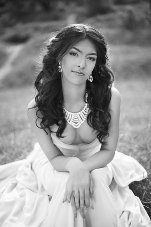 bride dress: Brunette bride in wedding dress resting and sitting on grass at spring park. beauty black and white portrait.