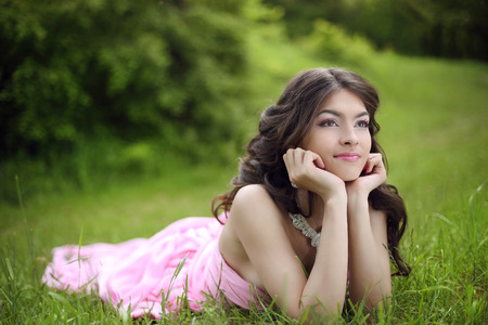 Attractive young teen girl with makeup wearing in pink dress lying on green grass field at spring park.