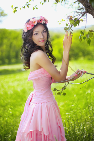 pretty hair: Beauty Romantic Girl Outdoors. Beautiful Teenage Model girl with flower chaplet posing in  green field at park