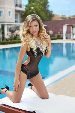 beautiful body: beauty fashion portrait of sexy girl model with makeup, long wavy hair style wearing bikini posing by swimming pool. having vacation