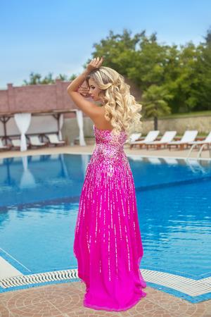 capelli lunghi: Bello modello della ragazza in abito rosa posa moda da blu piscina all'aperto. Donna bionda con il trucco, capelli ondulati lunghi e stile di lusso.