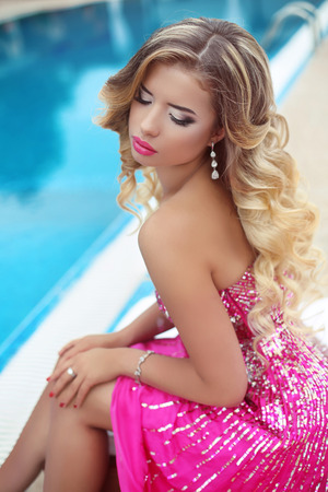 purple dress: Beautiful blond model girl in fashion pink dress with makeup and long wavy hair. Beauty woman, bright make-up. Purple lipstick and accessories.