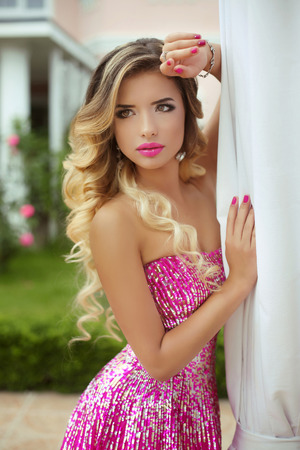 Beauty blond model girl in fashion pink dress with makeup and long wavy hair. Beautiful woman, bright make-up. Purple lipstick and accessories. Stock Photo