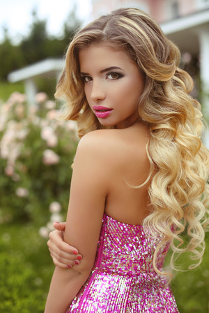 glamour girl: Makeup. Beautiful girl with blond long wavy hair posing in Fashion dress, attractive model in blossom park.