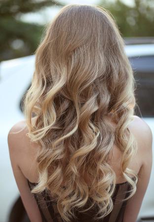 pelo: Cabello saludable. Peinado rizado largo. Volver la vista de cabellos rubios. cortes de cabello.