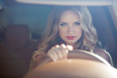portada: Hermosa sonriente que conduce el coche de la mujer, atractiva chica sentada en el automóvil, retrato al aire libre de verano. Foto de archivo