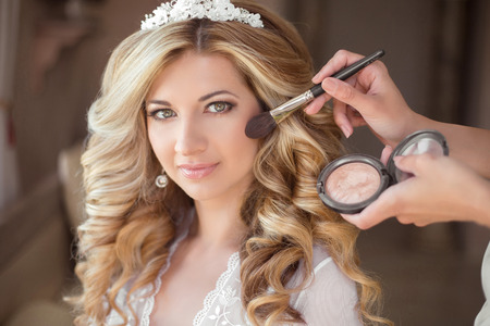 fashion make up: Make-up. Attractive smiling bride on the wedding day. Beautiful blond woman with long curly hair style. Professional Stylist makes makeup Stock Photo