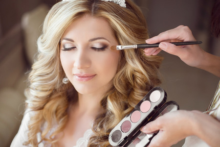 hair dresser: Beautiful bride girl with wedding makeup and hairstyle. Stylist makes make-up bride on wedding day. portrait of young woman at morning.