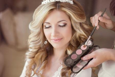結婚式のメイクと髪型の女の子を美しい花嫁。スタイリストの結婚式の日に花嫁メイクになります。朝の若い女性の肖像画。