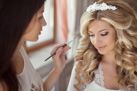 Beautiful bride wedding with makeup and hairstyle. Stylist makes make-up bride on wedding day. portrait of young woman at morning. Фото со стока