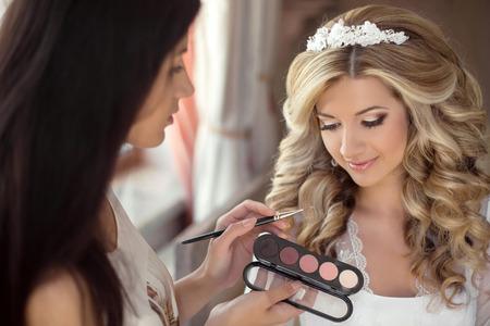 Stylist: Hermosa boda de la novia con el maquillaje y el peinado. El estilista hace novia maquillaje de día de la boda. retrato de mujer joven en la mañana. Foto de archivo