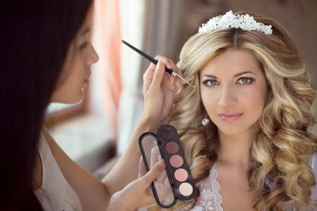 Stylist: Estilista Profesional hace que el maquillaje de la novia en el día de la boda. Hermosa mujer sonriente rubia con mucho estilo de pelo rizado.