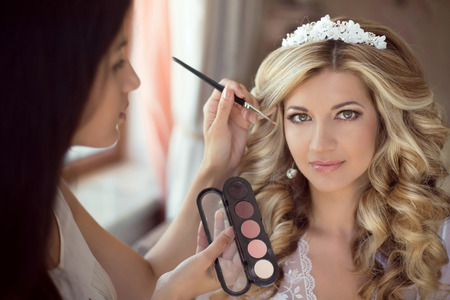 stylist: Professional Stylist makes makeup bride on the wedding day. Beautiful smiling blond woman with long curly hair style.