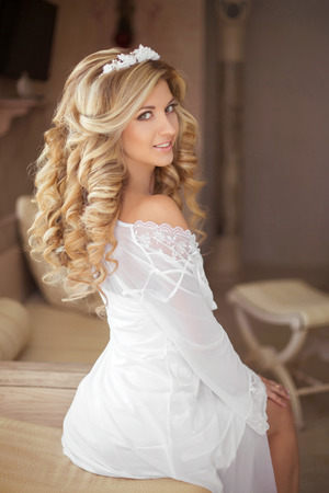 Healthy Hair. Beautiful smiling girl bride with long blonde curly hairstyle and bridal makeup posing at Wedding day. indoor portrait.