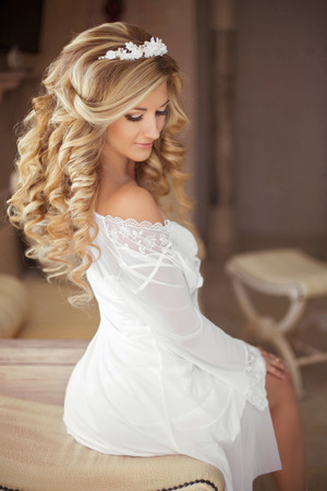 bridal hair: Healthy Hair. Beautiful smiling bride with long blonde curly hairstyle and bridal makeup. Attractive girl posing at Wedding day. indoor portrait.