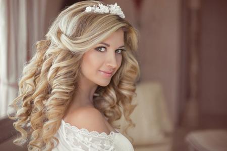 cabello: Cabello saludable. Novia hermosa muchacha sonriente con largo peinado rizado rubio y maquillaje de novia. Retrato de interior de la boda.