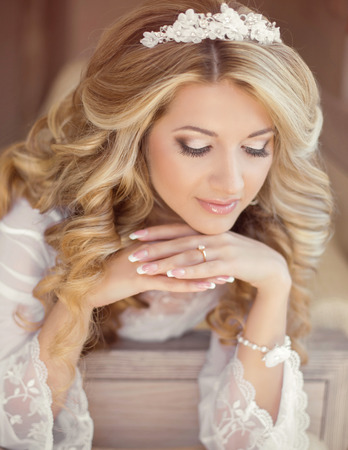 long: Beautiful bride woman indoor portrait. Makeup and wavy hair style. Manicured nails. Wedding morning day.