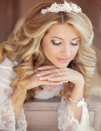 unas largas: Hermosa mujer novia retrato de interior. Maquillaje y peinado ondulado. Uñas cuidadas. Día de la boda de la mañana.