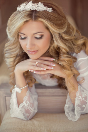 long day: Beautiful bride woman indoor portrait. Makeup and wavy hair style. Manicured nails. Wedding morning day.