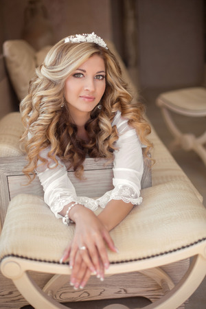 bride dress: Portrait of beautiful smiling bride with long curly hair posing on sofa at wedding morning. Makeup. Blonde girl in modern interior. Wedding dress. Stock Photo