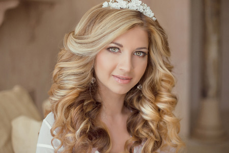 bridal salon: Beauty portrait of attractive smiling girl bride with long curly hair style and makeup at wedding day. Bridal morning concept.