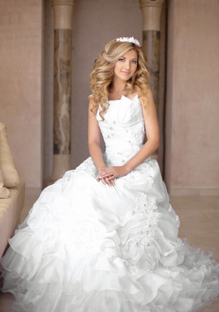 Attractive young smiling bride woman in wedding dress. Beautiful girl with curly hair style and professional bridal makeup posing in interior. Standard-Bild
