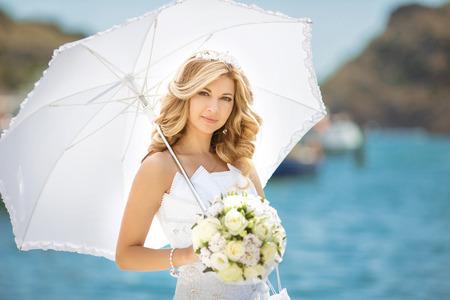 rubia ojos azules: chica bella novia en vestido de novia con el paraguas blanco y un ramo de flores, retrato al aire libre