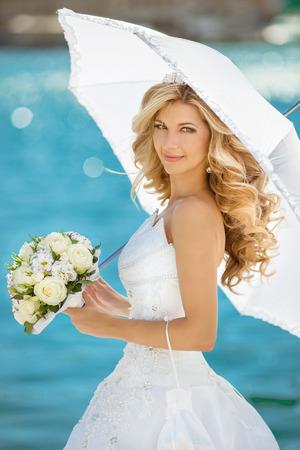 mazzo di fiori: Bella ragazza sorridente sposa in abito da sposa con ombrello bianco e bouquet di fiori, ritratto all'aperto