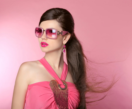 brunette girl: Beauty fashion model girl in sunglasses with bright makeup, long hair, manicured nails. Glamour woman isolated on pink studio background.