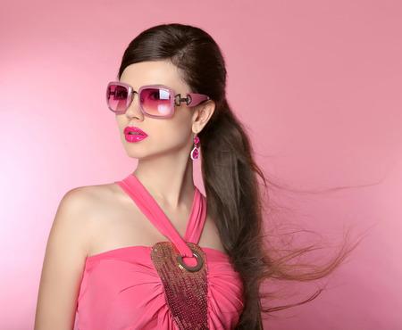 cola mujer: Muchacha de la belleza modelo de moda en gafas de sol con maquillaje brillante, cabello largo, las u�as cuidadas. Mujer del encanto aislado sobre fondo rosa estudio.