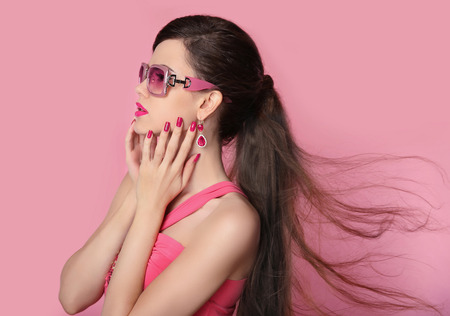 glamour hair: Beauty fashion model girl in sunglasses with bright makeup, long hair, manicured nails. Glamour woman isolated on pink studio background.