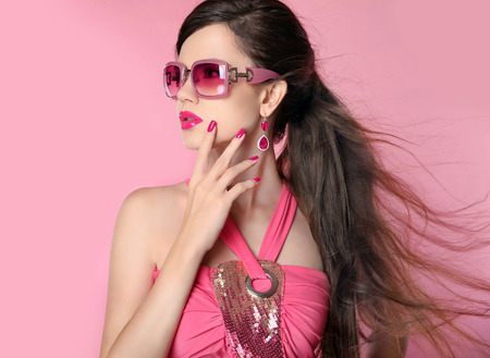long tail: Beauty fashion model girl in sunglasses with bright makeup, long hair, manicured nails. Glamour woman isolated on pink studio background.