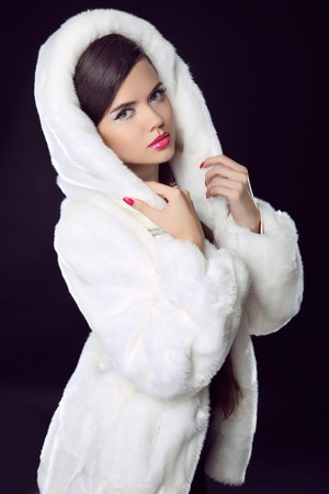 Beauty Fashion Model Girl in Mink Fur Coat and white furry hood. Beautiful Luxury Winter Woman isolated on black background.