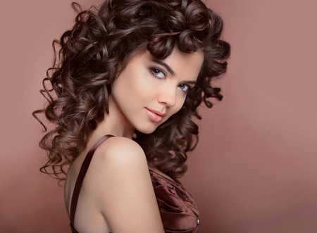 women face stare: Healthy hair. Beautiful young smiling woman with long curly hairs. Brunette with professional makeup.