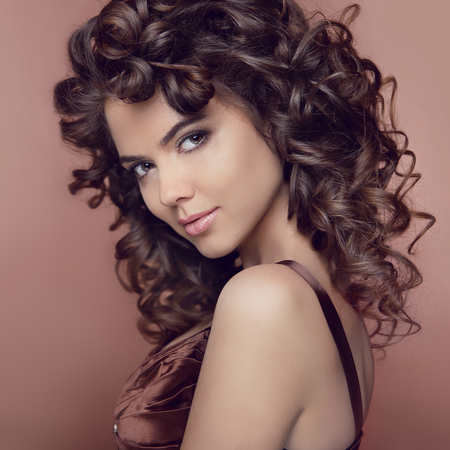 Wavy hair. Attractive smiling girl with makeup. Curly hairstyle. Brunette. Expressive eyes stare. Elegant lady over studio beige background. Luxury vogue style Archivio Fotografico