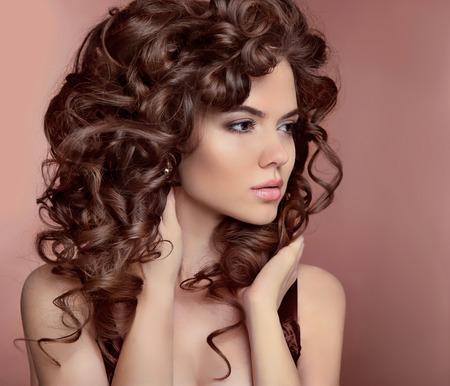 maquillage: Cheveux ondul�s. Belle fille avec le maquillage. Coiffure boucl�e. Brunette. Yeux expressifs regardent. Mode jeune femme isol� sur fond beige atelier. Le style de la mode de luxe Banque d'images