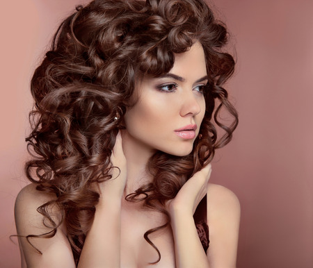 Wavy hair. Beautiful girl with makeup. Curly hairstyle. Brunette. Expressive eyes stare. Fashion young woman isolated on  studio beige background. Luxury vogue style Foto de archivo