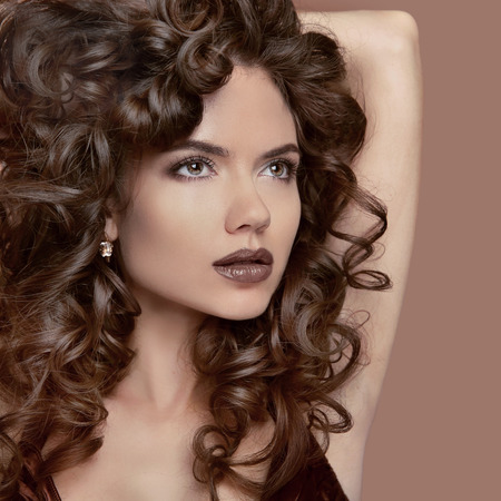 beige lips: Healthy curly hair. Beauty Makeup. Brunette girl model with fashion lips, wavy hairstyle. Beautiful woman isolated on beige studio background.
