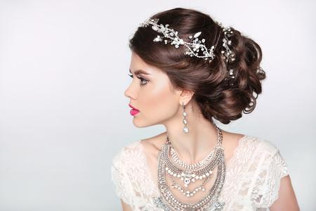 thời trang: Đẹp mô hình cô gái thanh lịch với đồ trang sức, trang điểm và tạo kiểu tóc retro. Bị cô lập trên nền studio.