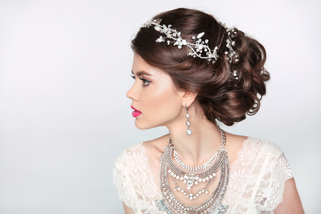 moda: Modelo hermoso de la muchacha elegante, con joyas, maquillaje y peinado retro cabello. Aislado en el fondo del estudio. Foto de archivo