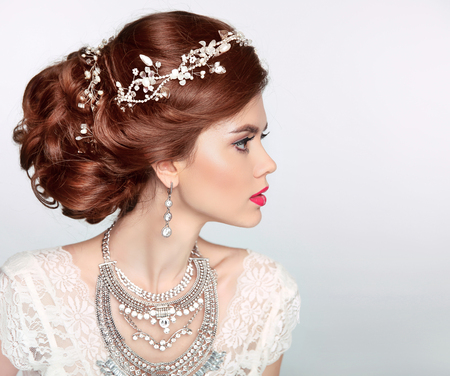woman hairstyle: Wedding Hairstyle. Beautiful fashion bride girl model portrait. Luxury jewelry.  Attractive young woman with red hair. Stock Photo