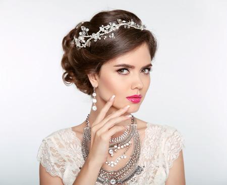 Kapsel. Aantrekkelijk meisje met make-up. Sieraden Earring. Expressieve ogen staren. Elegante dame die op studio witte achtergrond. Luxe stijl.