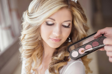 makeup a brush: Beautiful bride wedding with makeup and curly hairstyle. Stylist makes make-up bride on wedding day. Beauty portrait of young woman at morning.