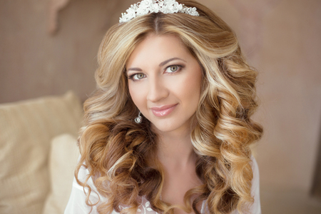 bridal hair: Healthy hair. Wedding makeup. Beautiful smiling girl bride with long blonde curly hairstyle.  bridal  indoor portrait.