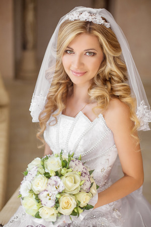 Beautiful smiling bride woman with bouquet of flowers, wedding makeup hairstyle, bridal veil. Girl wearing in white wedding dress 스톡 콘텐츠