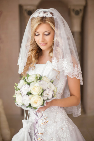 bride dress: Beautiful bride woman with bouquet of flowers, wedding makeup and hairstyle, bridal veil. Girl wearing in white wedding dress posing. indoor portrait.