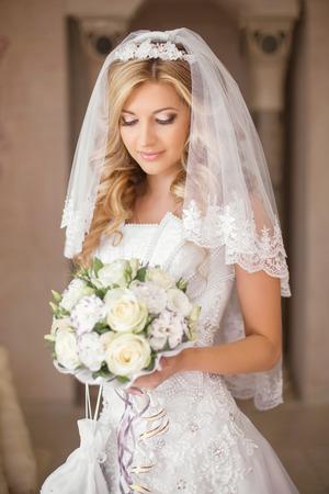 Mooie bruid vrouw met boeket van bloemen, bruiloft make-up en kapsel, bruidssluier. Meisje dat in witte trouwjurk poseren. indoor portret.