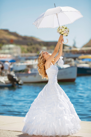 bride dress: Beautiful smiling bride girl in wedding dress with white umbrella and bouquet of flowers walking on seafront, outdoors portrait