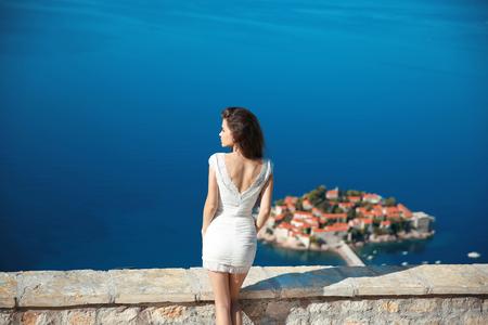 dress up: Beautiful brunette over blue sky posing in white dress. holidays, vacation, travel. Sveti Stefan island in Budva. Montenegro.