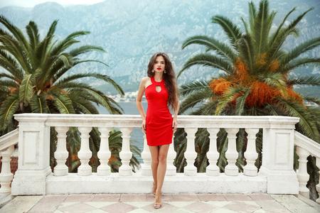 Mooi jong donkerbruin meisjesmodel in rode kleding die zich op Balkonmening bevinden op palmen en overzeese kust Kotor, Montenegro.